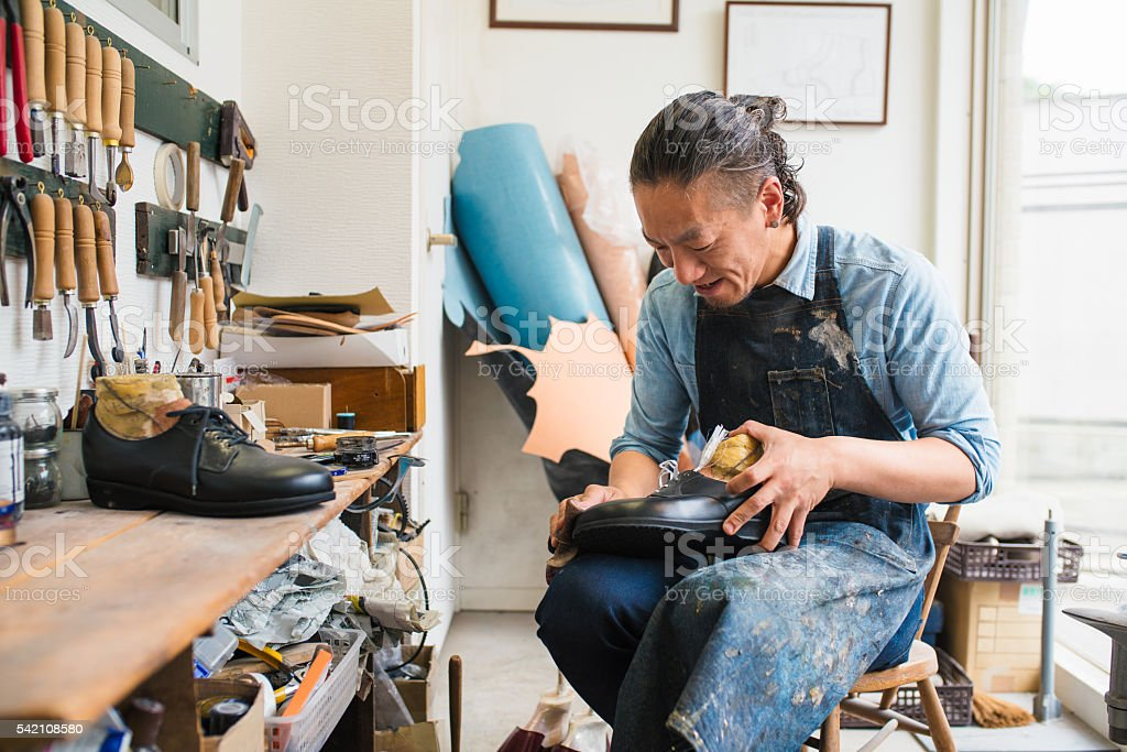Craftsman repairing or making a pair of shoes stock photo