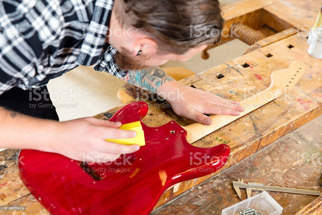 Craftsman sanding a guitar neck in wood at workshop stock photo