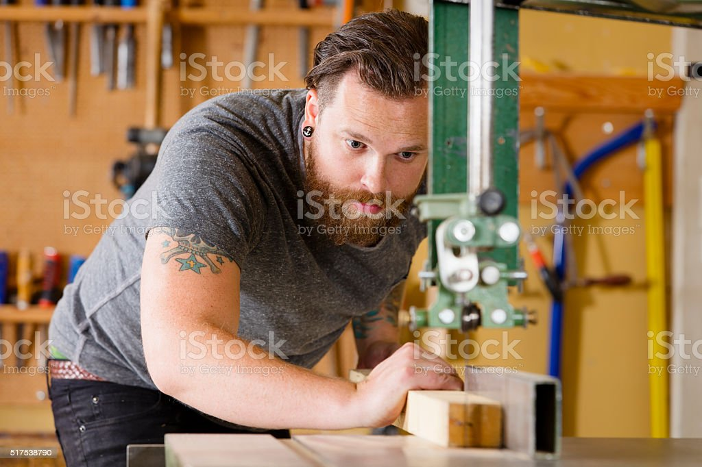 Craftsman using band saw for splitting wood plank in workshop stock photo