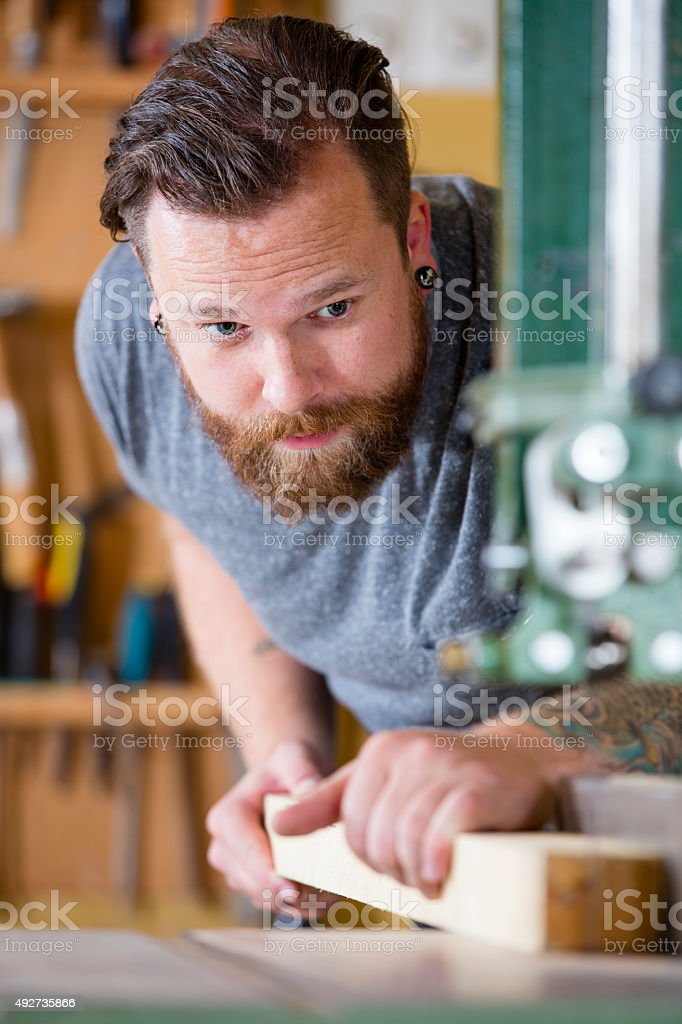 Craftsman using bandsaw for splitting wood plank in workshop stock photo