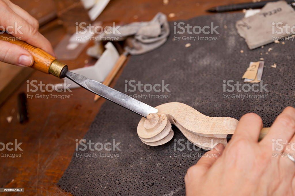 craftsman violin maker carving a neck in his laboratory stock photo