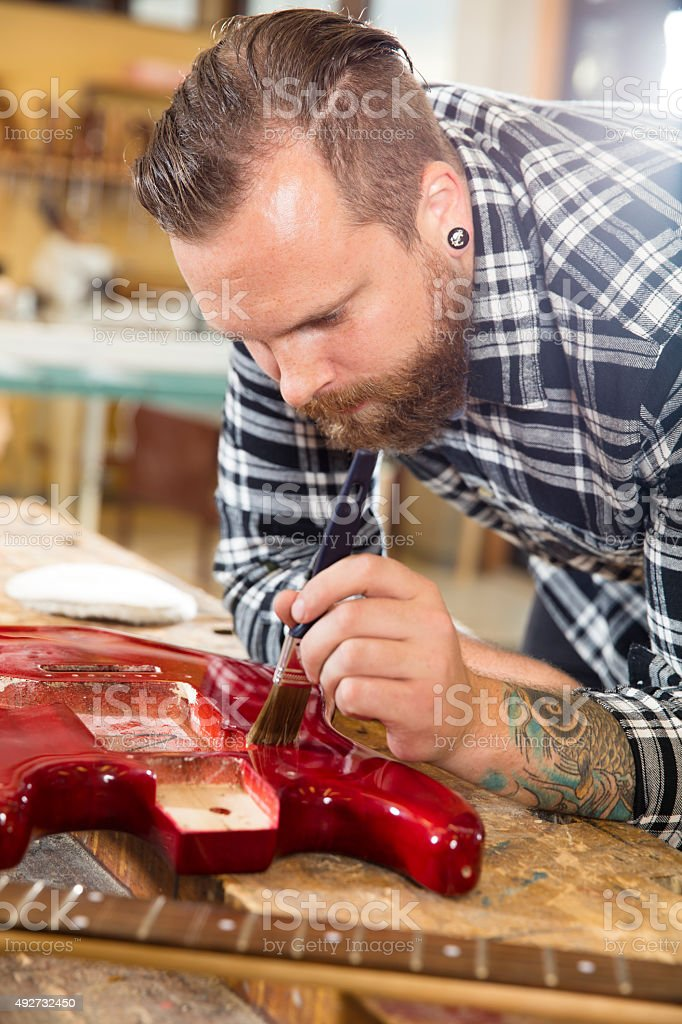 Craftsman working at workshop with musical instruments stock photo