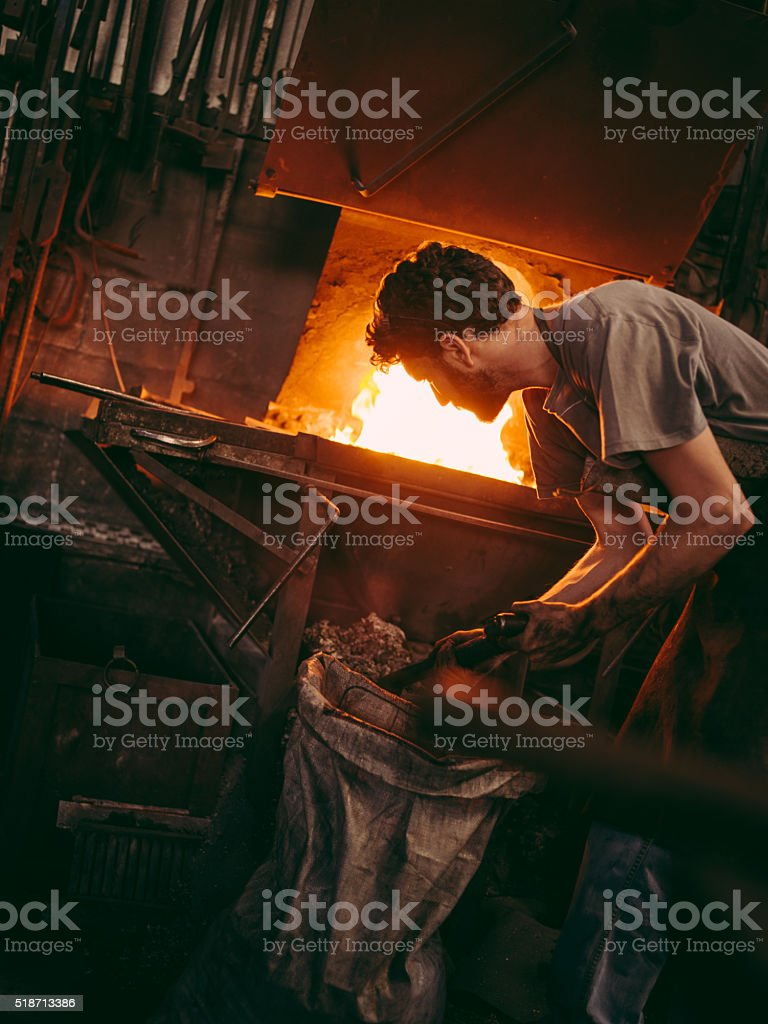 Craftsman working furnace in blacksmith's shop stock photo