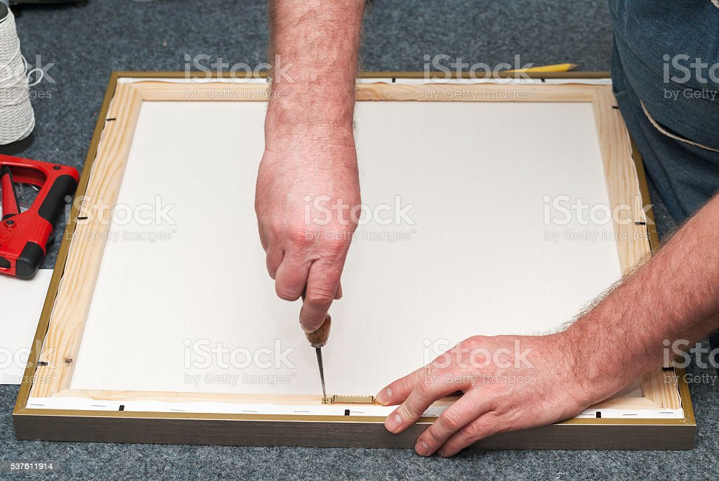Craftsman working on frame in frameshop. Copy space. Top view stock photo