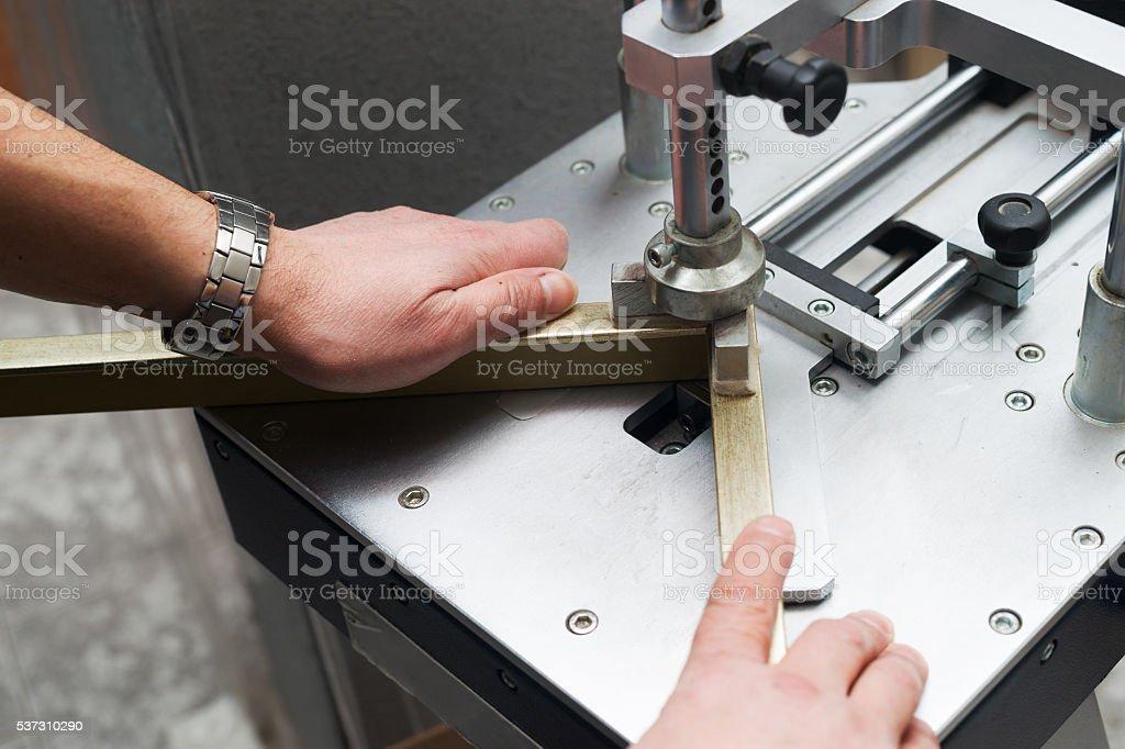 Craftsman working on frame in frameshop. stock photo