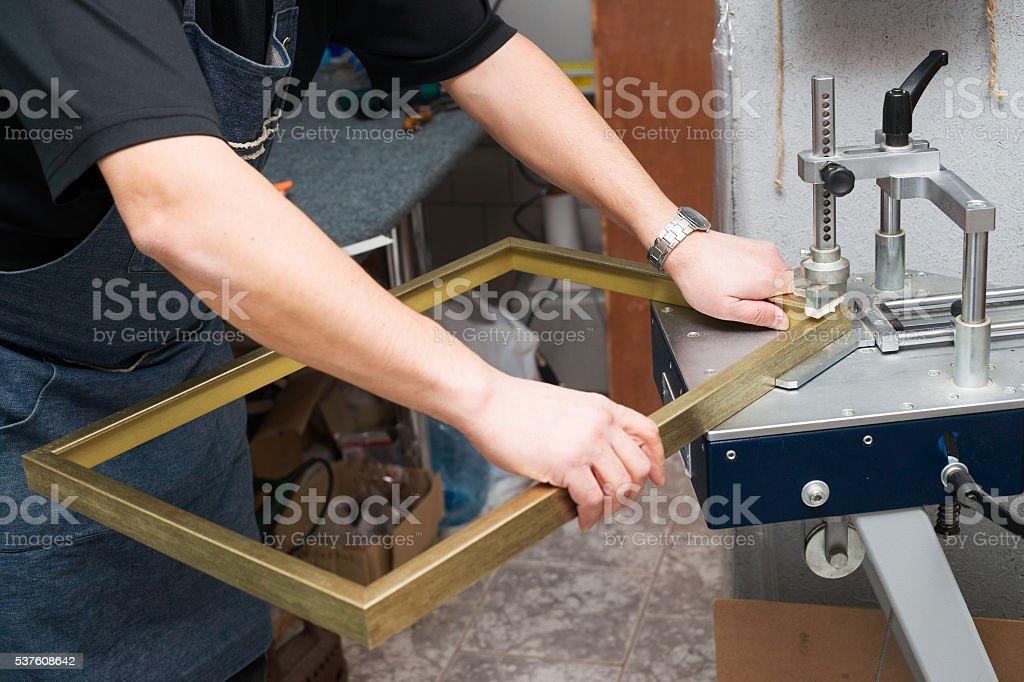 Craftsman working on frame in frameshop. Professional framer. Top view. stock photo