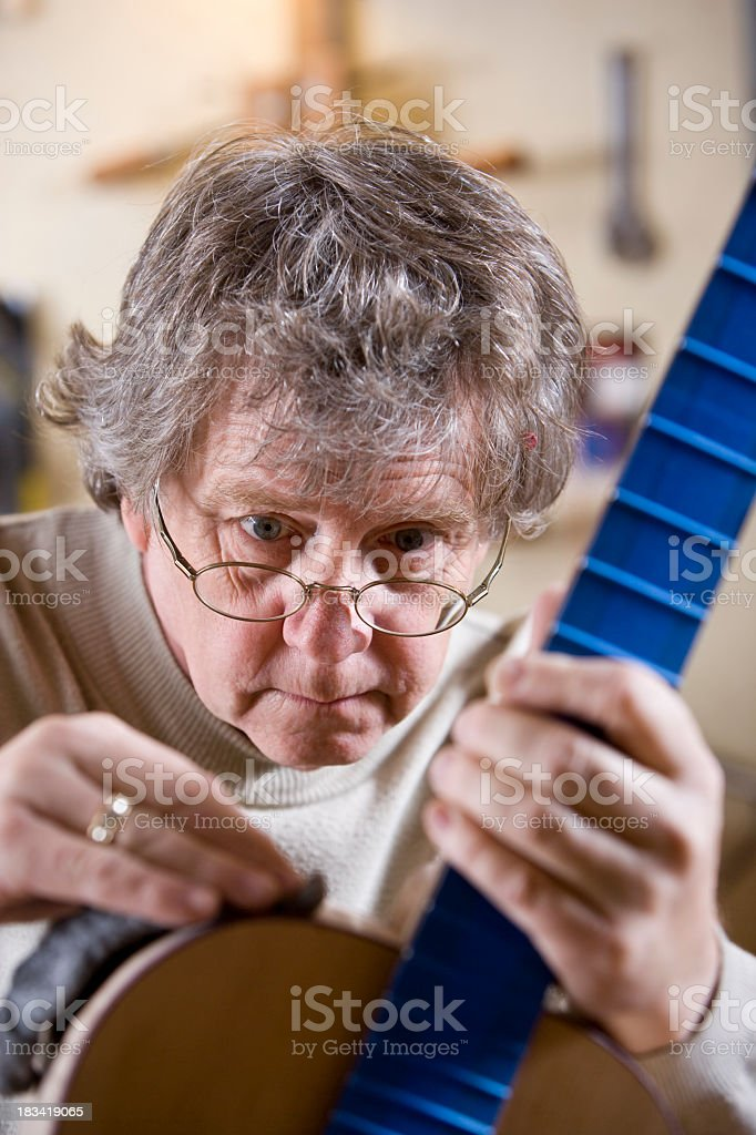 Craftsman working on guitar stock photo