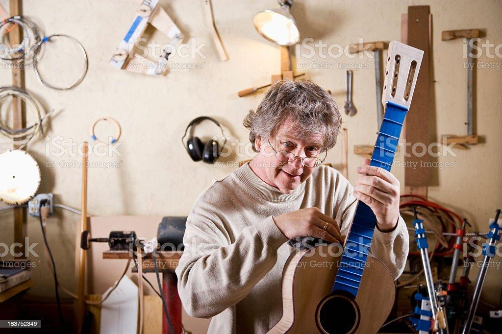 Craftsman working on guitar stock photo