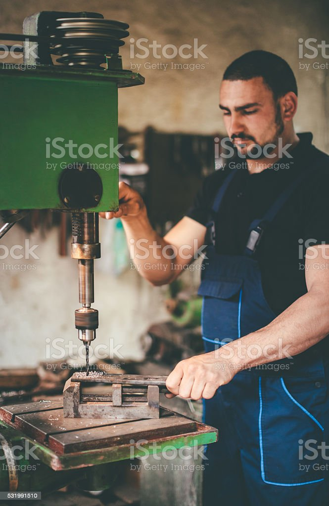 craftsman working with drill stock photo