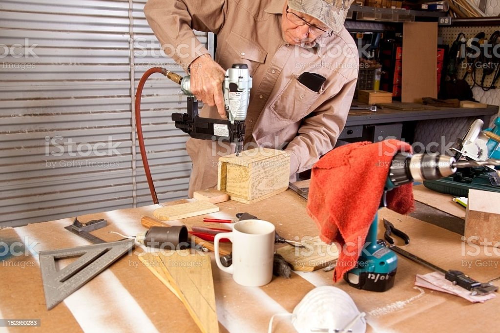 Craftsman working with nail gun real workshop workbench royalty-free stock photo