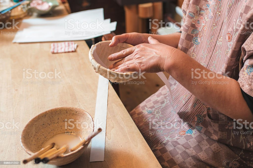 Craftsperson adding strips of paper to a handmade bowl stock photo
