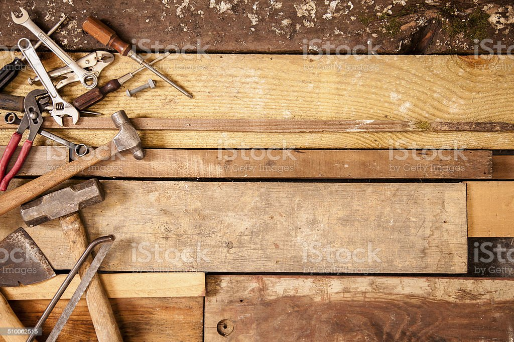Craftsperson, carpenter tools to left side. Old wooden boards background. stock photo