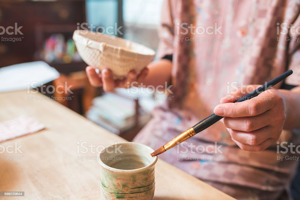 Craftsperson handpainting a paper bowl stock photo