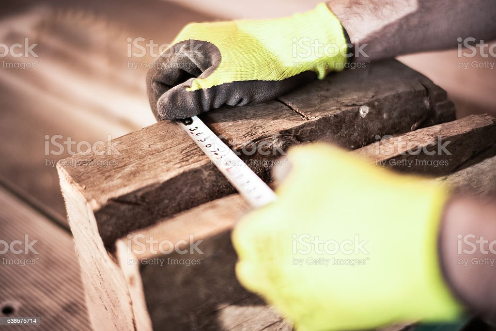 Craftsperson measuring wood stock photo