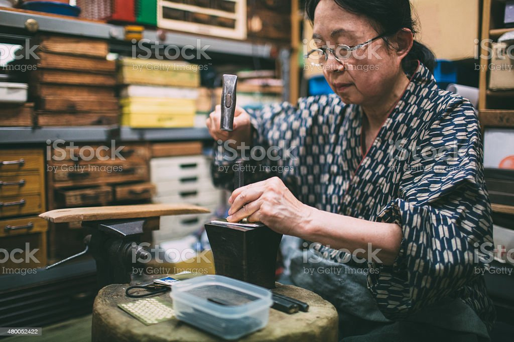 Craftswoman working on metal ornaments stock photo