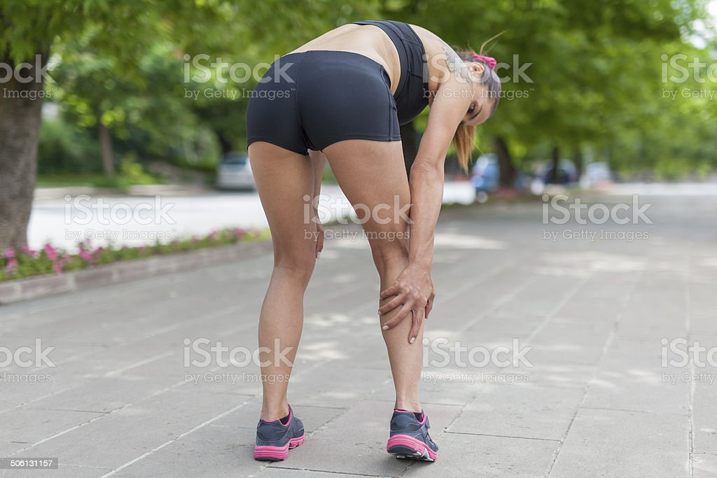 cramp in leg calf during jogging stock photo