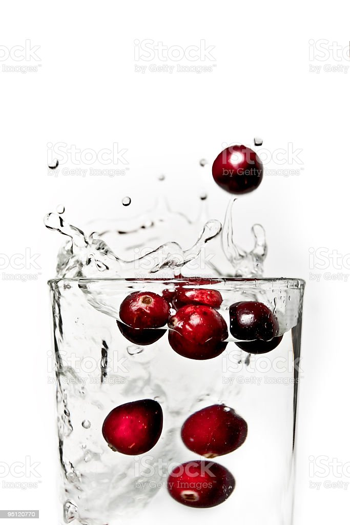 Cranberries splashing in a glass of water. royalty-free stock photo