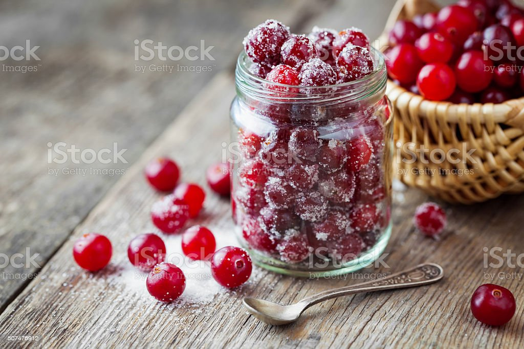 Cranberries with sugar in glass jar, basket with berries stock photo