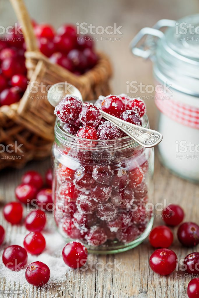 Cranberries with sugar in glass jar, wicker basket with berries stock photo