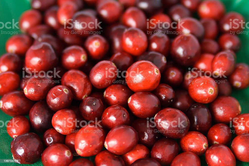 Cranberry berries on a green background royalty-free stock photo