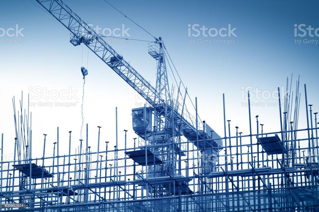 Crane and building construction site against blue sky stock photo