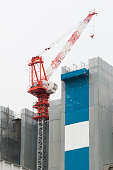 Crane and building construction site with white background.