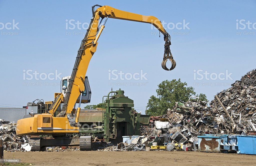Crane and metal compactor at recycling facility stock photo