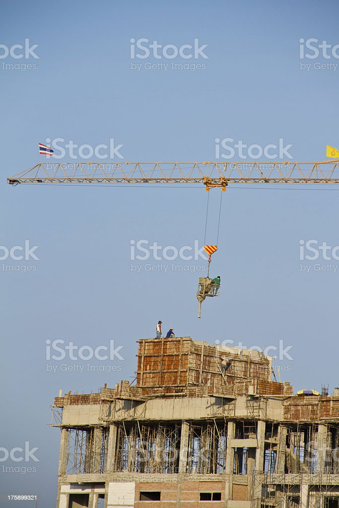 Crane and workers at construction site royalty-free stock photo