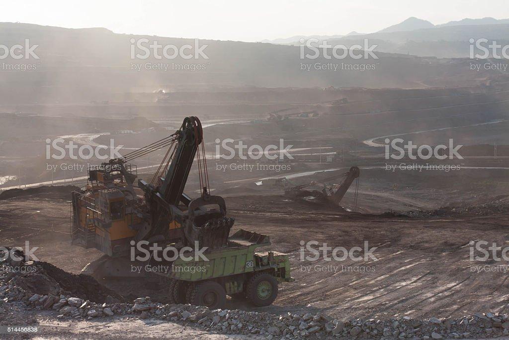 Crane bucket loading iron ore into truck at mine stock photo