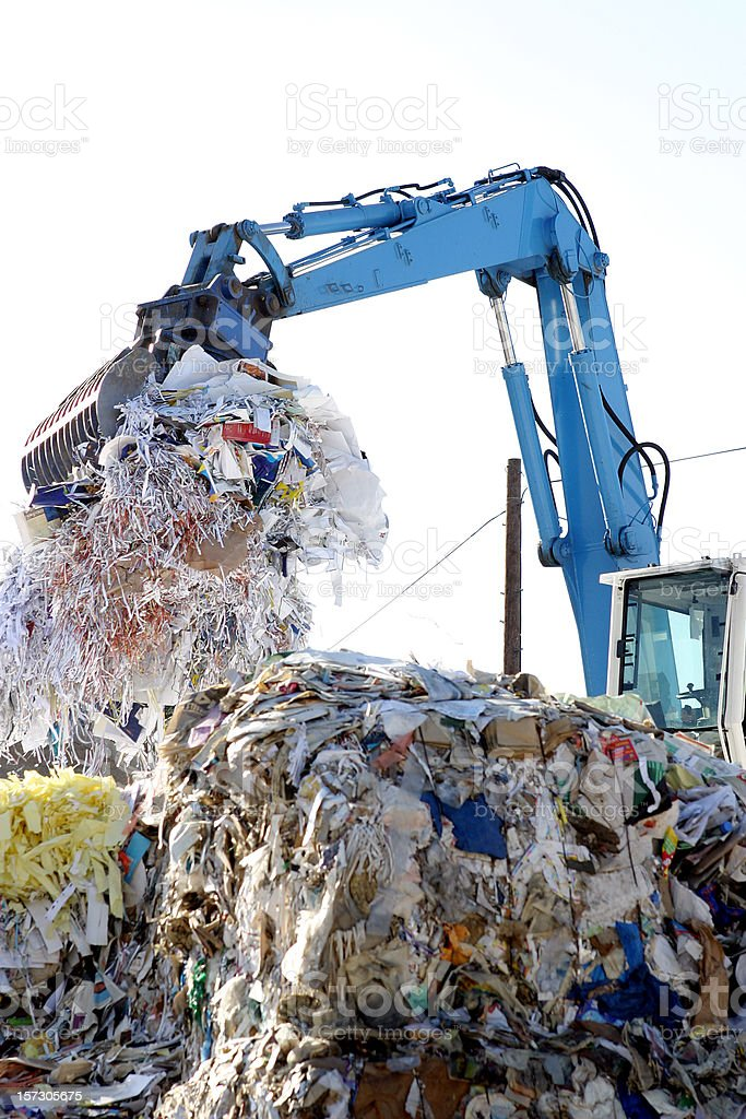 Crane carrying paper to be recycled at waste collection royalty-free stock photo
