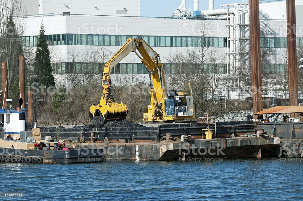 Crane depositing dredged soil from river bottom onto barge royalty-free stock photo