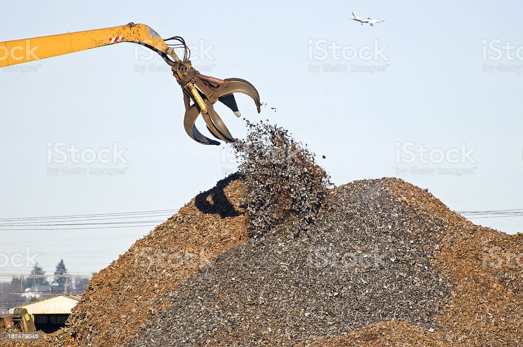 Crane depositing shredded metal on pile royalty-free stock photo
