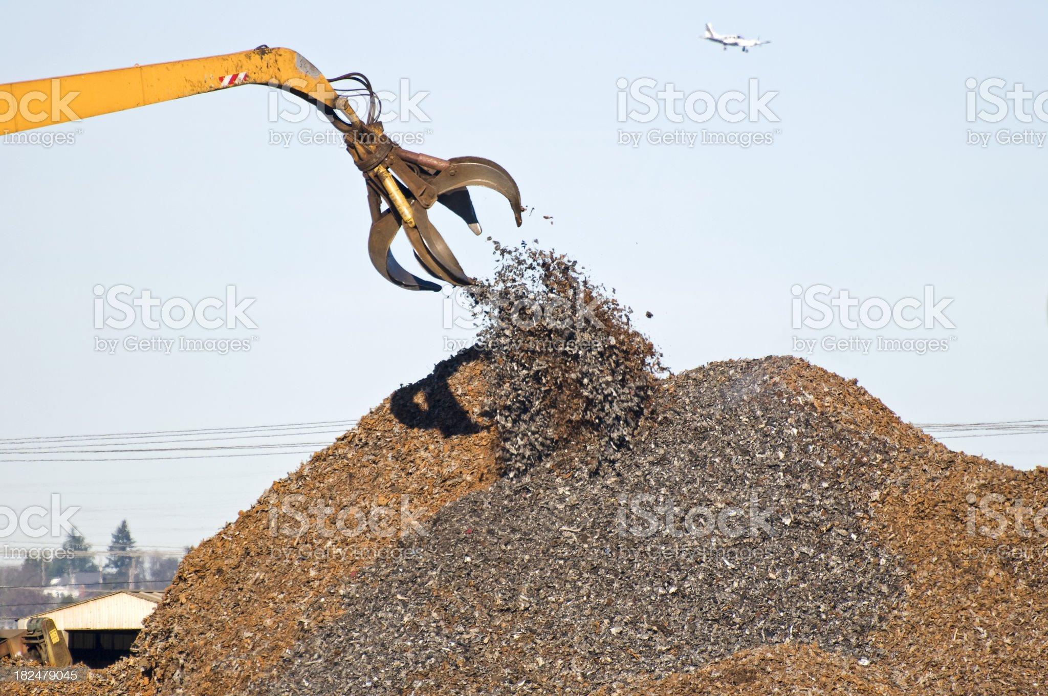 Crane depositing shredded metal on pile royalty-free stock photo