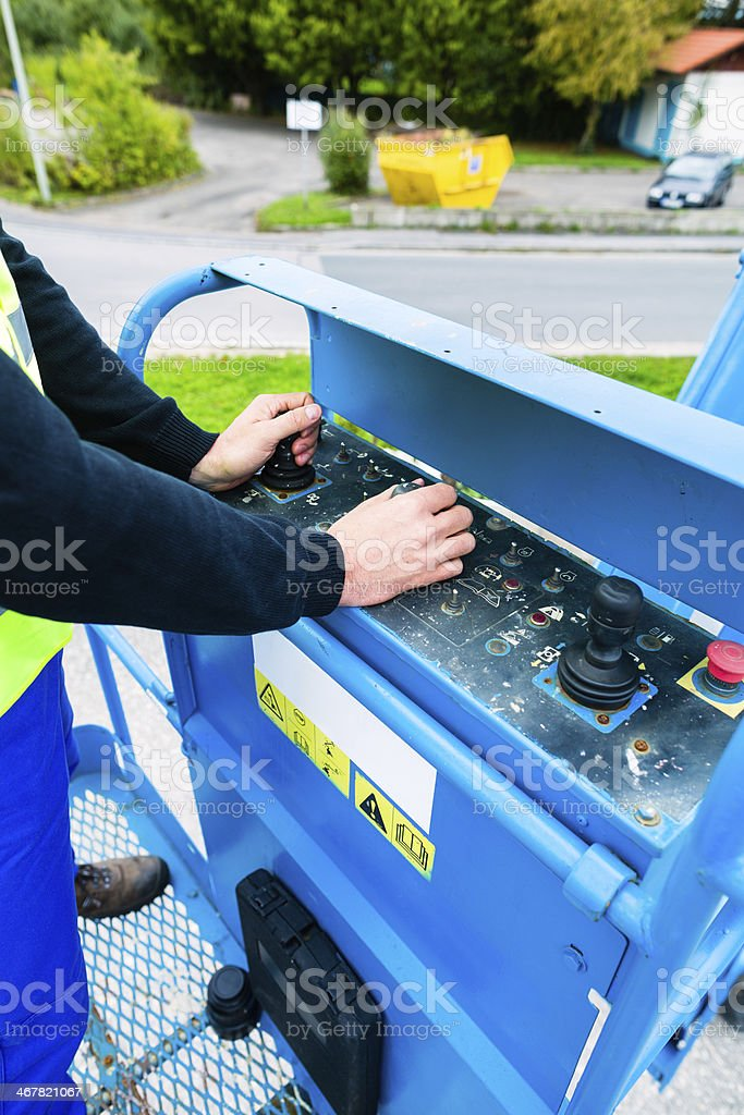 Crane driver driving hydraulic lifting ramp with control desk stock photo