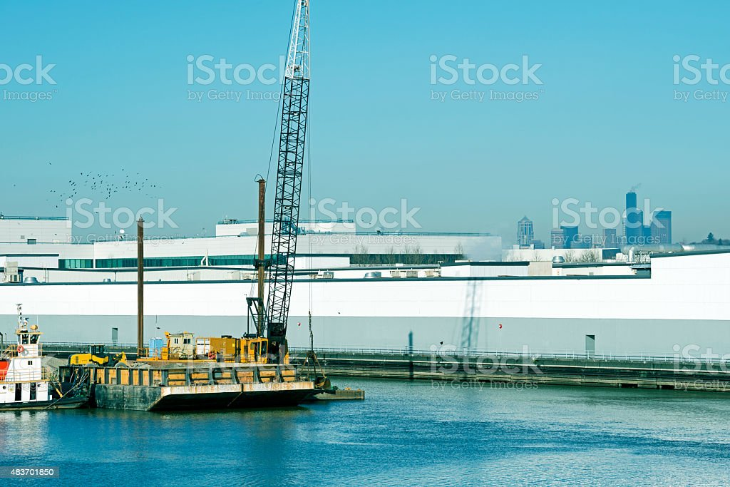 Crane dropping gravel on bottom of polluted industrial waterway stock photo