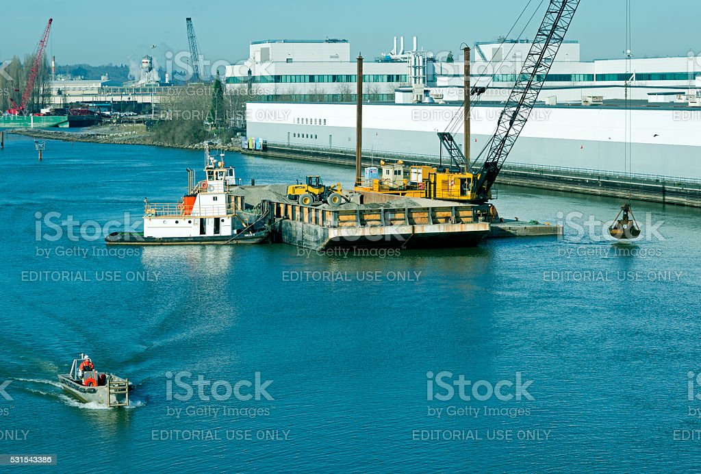 Crane dumping gravel in waterway as part of cleaning project stock photo