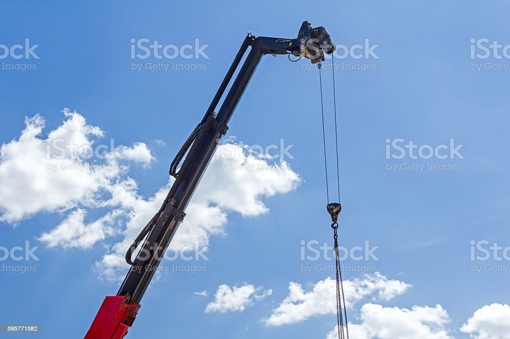 Crane hook with chain is hanging above building site stock photo