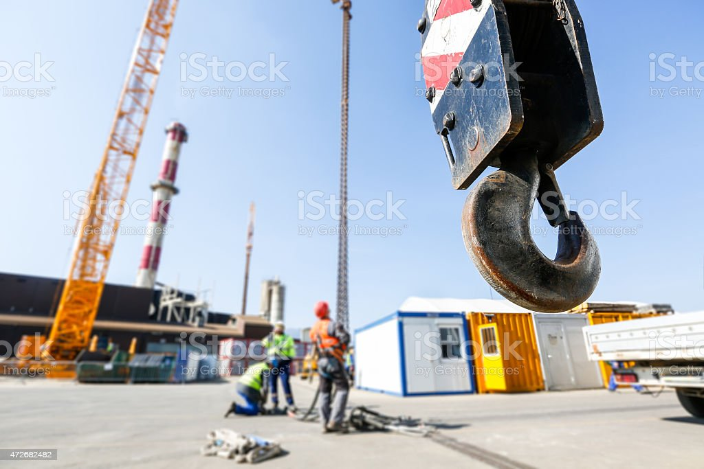 Crane hook with workers in the background stock photo