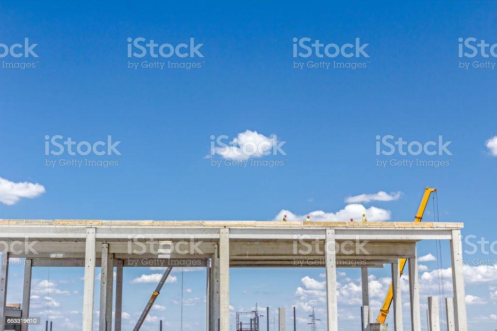 Crane is working on edifice, concrete skeleton against blue sky. stock photo