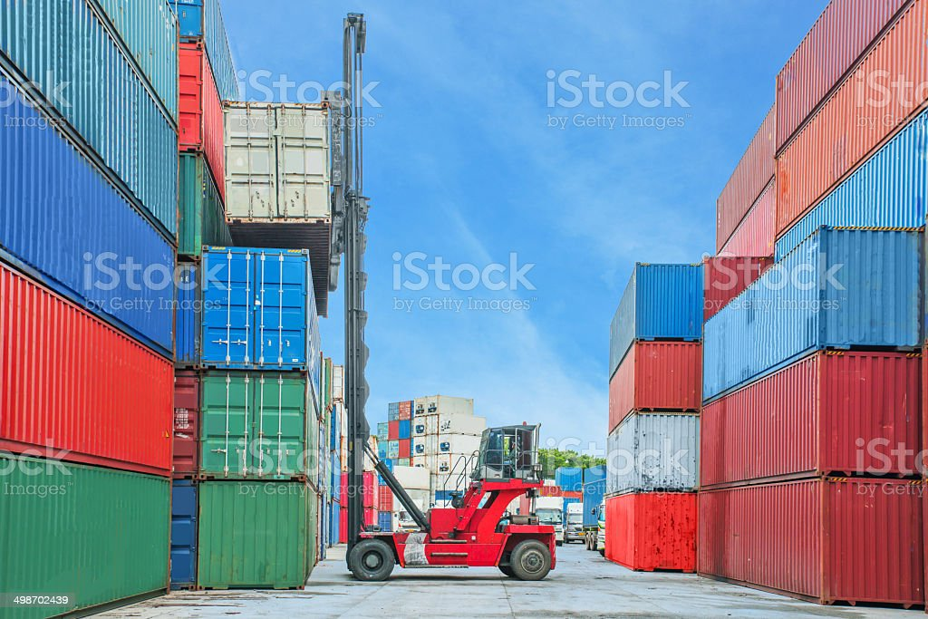 Crane lifter handling container box loading to truck in import stock photo