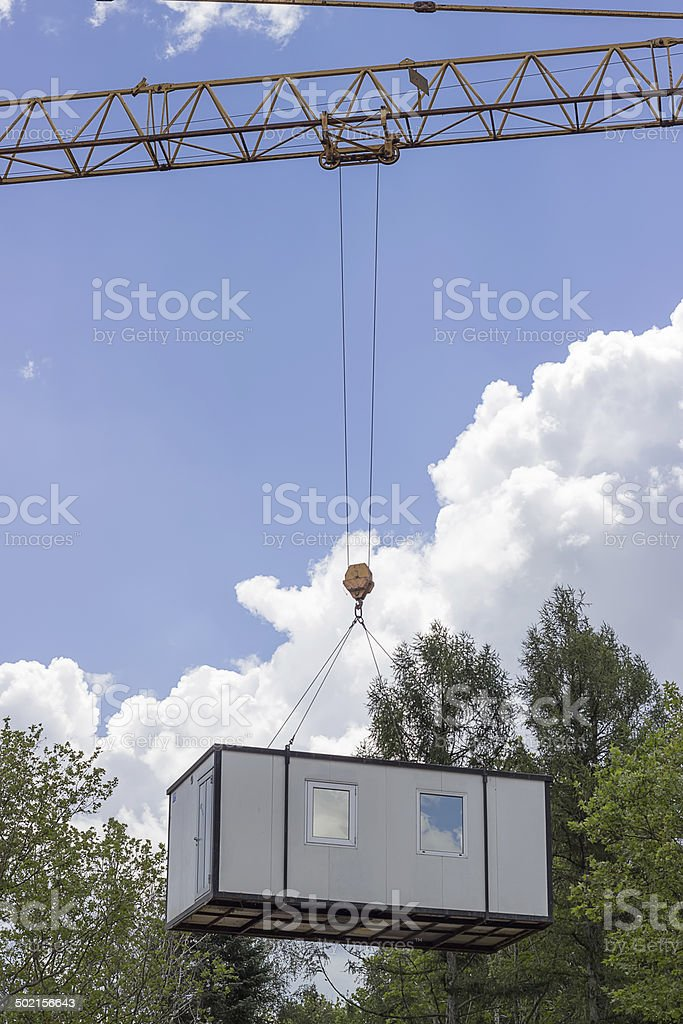 crane lifting and moving container house stock photo