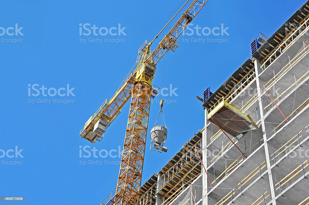 Crane lifting cement mixing container stock photo