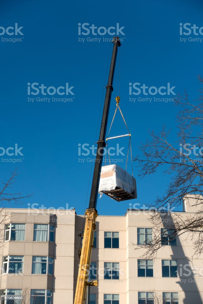 Crane Lifting HVAC Unit stock photo
