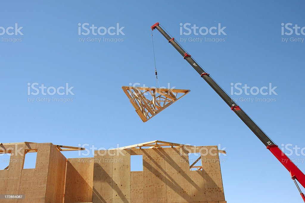 Crane lifting roof truss stock photo