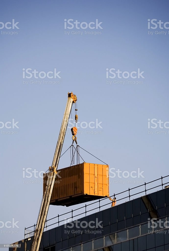 crane loading container to building roof stock photo