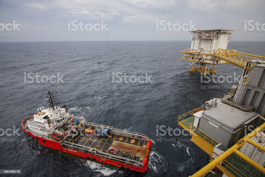 Crane operation with supply boat stock photo