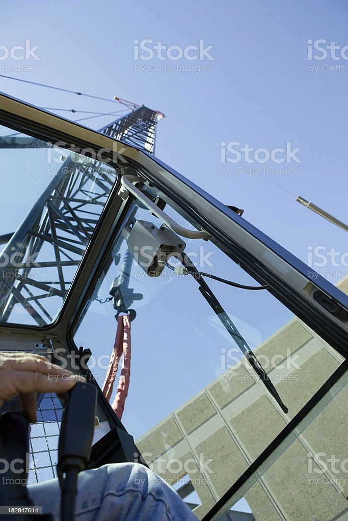 Crane Operator Raising New Roof Beam at Commercial Construction Site royalty-free stock photo