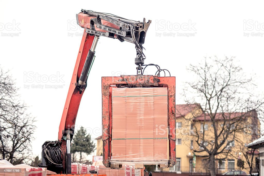 Crane or industrial forklift delivers a brick pallet stock photo