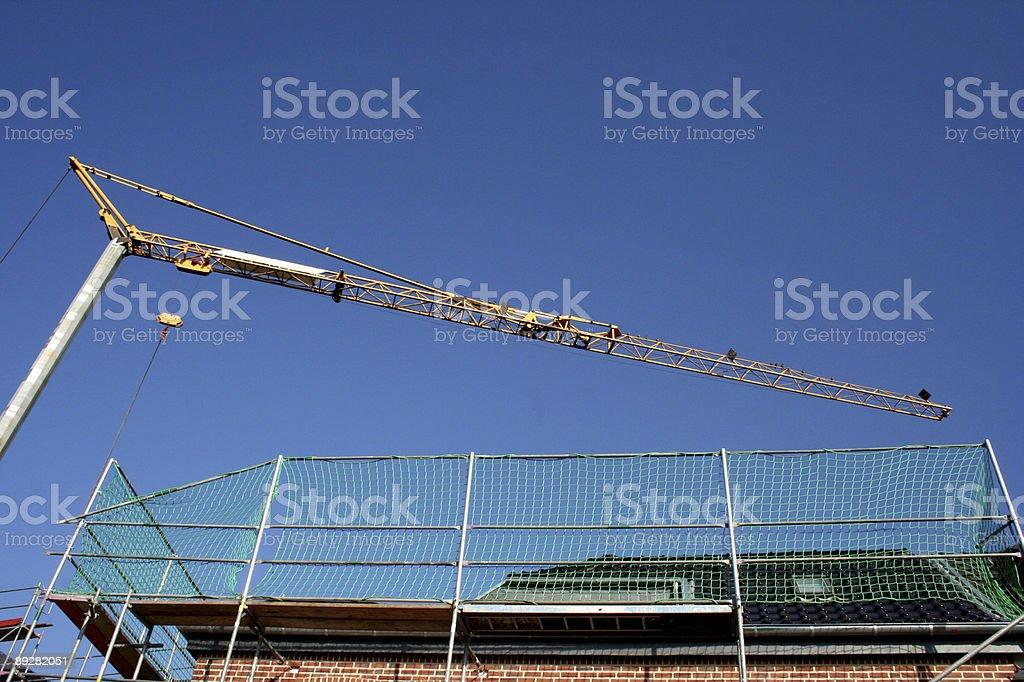 crane reaching over scaffolding royalty-free stock photo