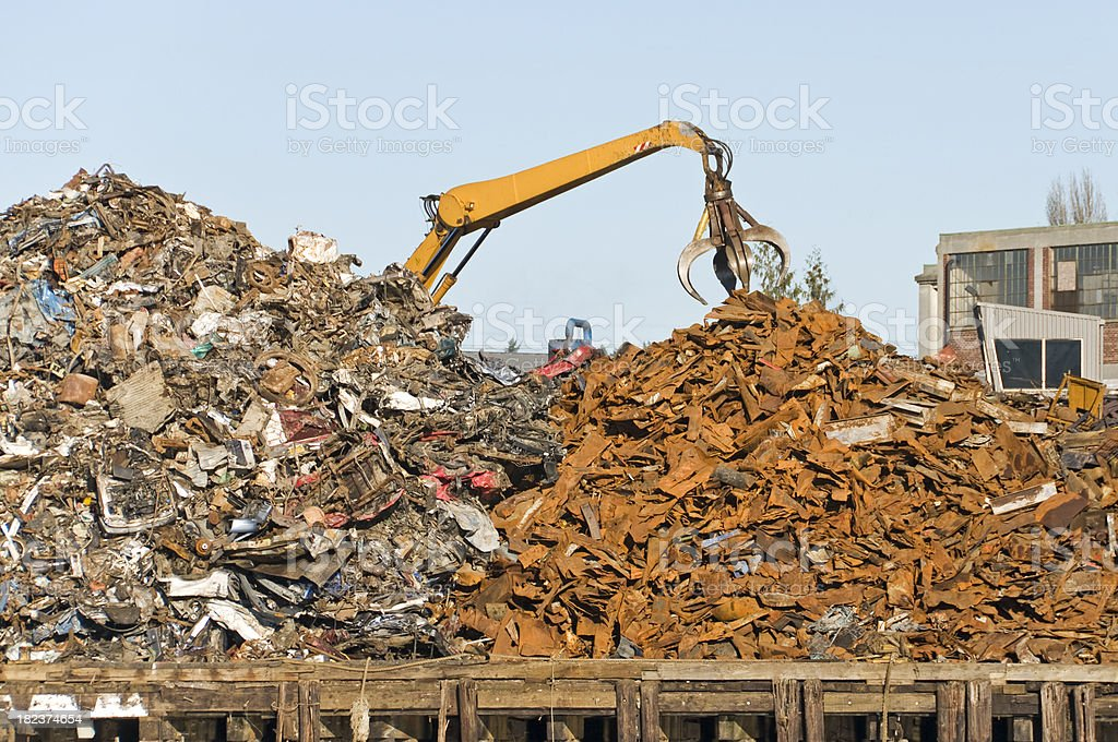Crane releasing scrap metal at recycler royalty-free stock photo